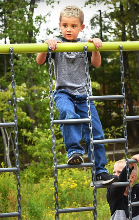 "BRYAN EATON/Staff Photo. Kristiano Pereira, 6, climbs to the top of the chain ladder at the playground at Partridge Brook Park behind Salisbury Elementary School on Friday afternoon during ""unified arts"" where children spend time together with the physical education, art and music instructors doing different things in in their respective fields. The playground was built in May with help from Timberland employees and those from town hall and the DPW with funds from a Housing Choice Grant."