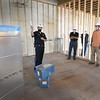 BRYAN EATON/Staff photo. Deputy Chief John Lucey, left, shows the locker room and shower area of the new police station to selectman Geoff Walker, Bob Connors and selectman JR Colby.