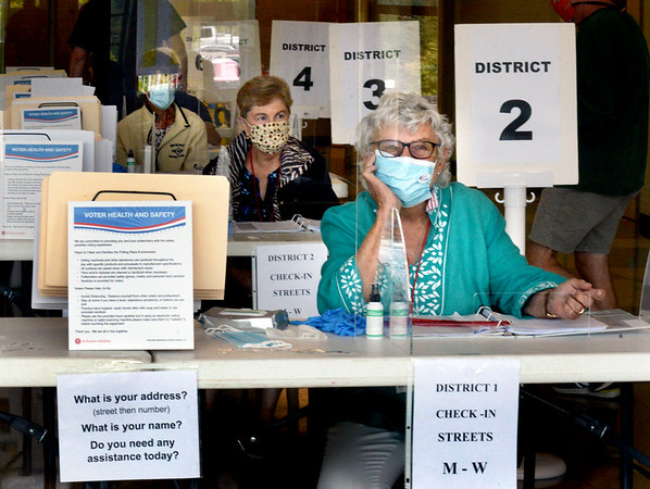 BRYAN EATON/Staff Photo. Behind plexiglass and a mask, Cherie Antle, who's been a poll worker for over 20 years, and others wait for voters in Amesbury High School on Tuesday morning.