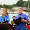 """JIM VAIKNORAS/Staff photo Ariadne Nevin and Thomas Jacobs sing """"A Song of Peace""""  during the Relocation Ceremony for the Newburyport Fisherman's Memorial on the boardwalk on the Newburyport Waterfront Monday morning."""