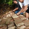 BRYAN EATON/Staff photo. Newburyport High School teacher Jay Martel, left, works with student Jaden Medeiros, 17, sorting through used bricks for reuse at the Crow Lane yard waste facility. The school's seniors were doing community projects around town.