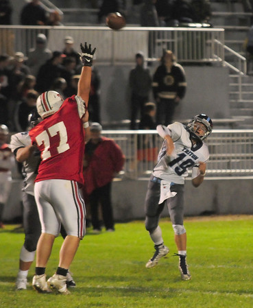 JIM VAIKNORAS/Staff photo Triton's Lewis L'Heureux throws a pass over the reach of Amesbury lineman Elijah Huynh at Amesbury Friday night.