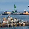 BRYAN EATON/Staff photo. New boulders are put into place at the north jetty of the Hampton River as more are stored on a barge in the foreground.