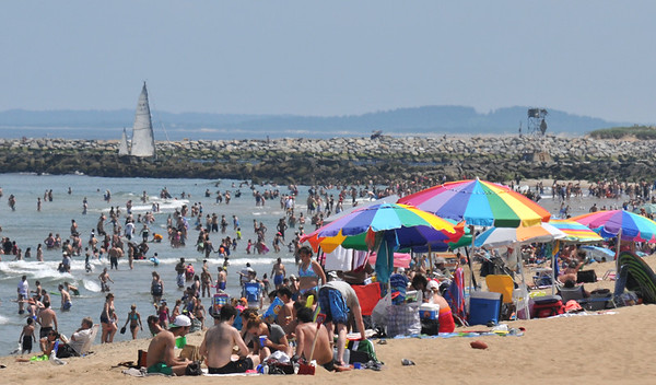 JIM VAIKNORAS/staff photo A sailboat glides up the Merrimack River past a crowded Salisbury Beach State Reservation on a hot 4th of July afternoon. Jim Vaiknoras/staff photo