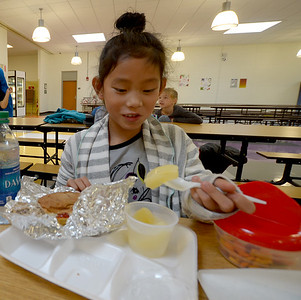 JIM VAIKNORAS/Staff photo 4th grader Nora Greerling, 10, enjoys some peaches with her chicken sandwich during lunch at the Molin Elementary School in Newburyport.