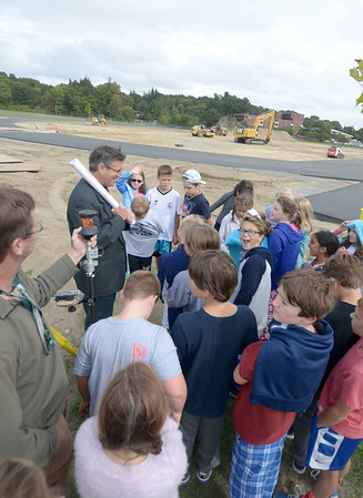 JIM VAIKNORAS/Staff photo Huntres Sports president Chris Huntress and surveyer Everett Chandler gives students from llyson Kusser 5th grade class at the Molin a tour of renovations of Fuller Field in Newburyport. The tour was part of the program on engineering and design.