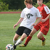BRYAN EATON/Staff photo. Jack Queenan moves the ball with Masconomet's Grady Kozack in pursuit.