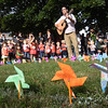 "BRYAN EATON/Staff photo. Newburyport Montessori School music teacher Neil Ferreira leads youngters in the song ""Light a Candle For Peace"" Thursday morning outside the Unitarian Church. They were participating in the International Day of Peace in conjunction with Montessori schools from across the globe with that song starting on the shores of New Zealand and travelling from country to country, continent to continent and time zone to time zone until it reached the Hawaiian Islands 24 hours later."