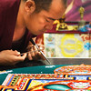 BRYAN EATON/Staff photo. Jampa Nordu taps a stylus holding the heavy, fine sand to create the mandala painting.