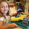BRYAN EATON/Staff photo. Ellie Cataldo, 5, heads to join classmates at the dining table to feast on the corn and rest of their lunch.
