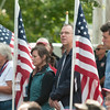 JIM VAIKNORAS/Staff photo People stand among  the flags at the Field of Honor ceremony on the Bartlet Mall in Newburyport Sunday afternoon.