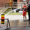 BRYAN EATON/Staff photo. Amesbury firefighter Chris LeSage helps Sean Mitchell aim a firehose at a target at Coastal Connections in Amesbury. The fire department was on hand to give tips on fire safety followed by demonstrations and the police department gave a K-9 demonstration as well.