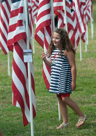 JIM VAIKNORAS/Staff photo Charlotte Walton, 7, of Newbury walks through the flags at the Field of Honor ceremony on the Mall in Newburyport Sunday afternoon. Charlotte's god father Specialist Chris Adams of Groveland is a Combat Medic with the 946th Forward Surgical Team serving in Afganistan.