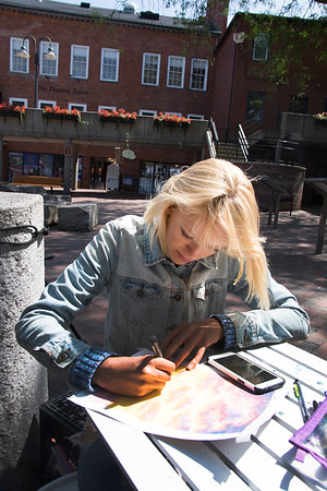 JIM VAIKNORAS/Staff photo Chloe Pienaar of Winshester sketches a picture on Inn Street in Newburyport Friday. She was in Newburyport to sell her art work and to promote her Etsy site, creativelycarefree, she is hoping to raise money for art school.