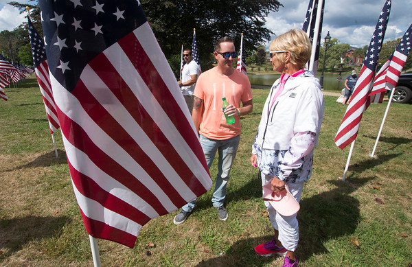 JIM VAIKNORAS/Staff photo Nancy Roy and her son Matt Roy look at a flag honoring their husband and father Mike Roy at the Field of Honor ceremony on the Bartlet Mall Sunday.