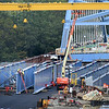 BRYAN EATON/Staff photo. Iron workers tend to the huge I-beam that support the roadway deck of the southbound span of the Whittier Bridge in a view from the Ferry Road overpass in Newburyport on Thursday afternoon. The bridge, which has had a couple delays, is scheduled to open in the spring.