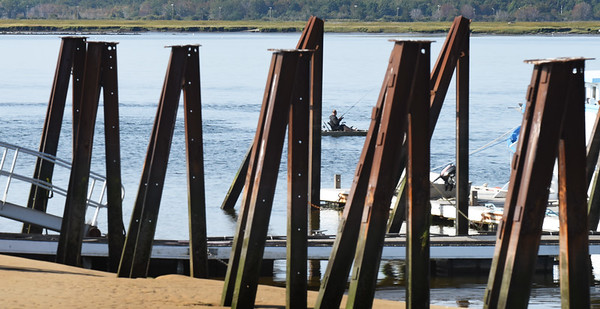 BRYAN EATON/Staff photo. A fisherman casts his line in the Merrimack River in a view through the pilings at Plum Island Point. The rest of the week looks sunny and warm though some rain is possible Friday.