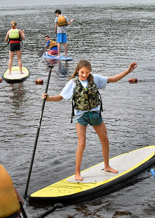 BRYAN EATON/Staff photo. Amesbury Middle School student Olivia Levasseur tries to balance on a paddle board at Lake Gardner Beach on Thursday morning. The students were learning the basics of paddle boarding and kayaking on quite a windy day.