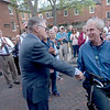 JIM VAIKNORAS/Staff photo 	Jonathan Woodman, sitting, shakes hands with Jack Bradshaw on Inn Street in Newburyport Saturday. JTHe pair were honored for their work in helping restore the city in the '70s and '80s.