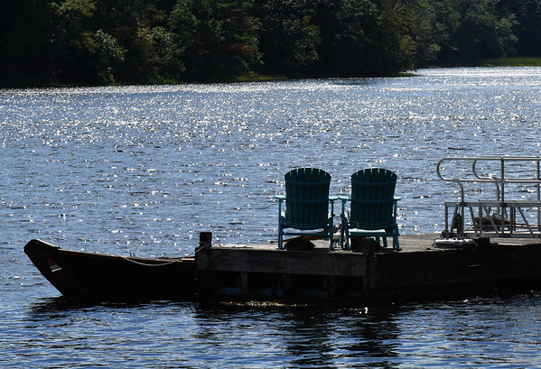 BRYAN EATON/Staff photo. Late afternoon sun twinkles on the Merrimack River at Point Shore in Amesbury past there Adirondack chairs which would be a nice place to be this weekend. The air is forecast to be warm for awhile yet before fall begin in two weeks.