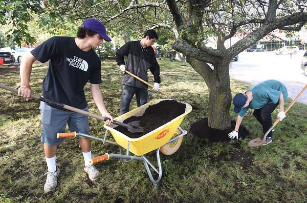 BRYAN EATON/Staff photo. Newburyport High School seniors spruce up the park area in front of the Green Street parking lot on Merrimac Street on Tuesday, from left, Matt Martin, Kyle Menard and Bradley Moore. Seniors were around the city for their annual day of community service.