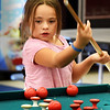 BRYAN EATON/Staff photo. Olivia Parada, 7, of Salisbury watches her shot follow through in a game of bumper pool at the Boys and Girls Club. Monday was the first day of their afterschool programs.
