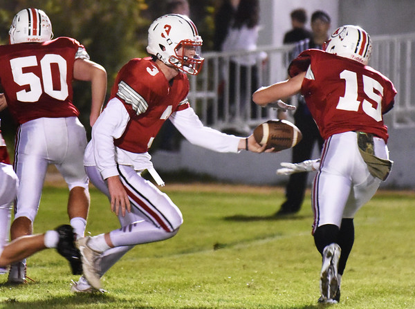 BRYAN EATON/Staff photo. Logan Burrill gets the handoff from Blake Bennett.
