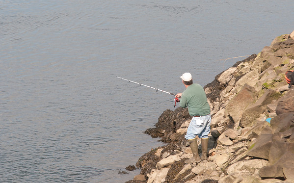 JIM VAIKNORAS/Staff photo A man fishes in the Plum Island River from the rocks under the Sgt. Donald A. Wilkinson Bridge in Newbury Monday afternoon.