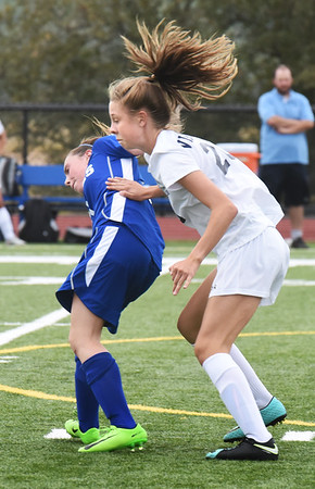 BRYAN EATON/Staff photo. Georgetown's Rylie Lasquade, left, and Triton's Emily Colby clash trying to get the ball.