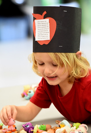 BRYAN EATON/Staff photo. Brayden Pimental, 4, plays with toys from the Littlest Pet Shop in Jayne Keeler's kindergarten class at Salisbury Elementary School while wearing a special hat with an apple on the front. The students were read a book about Johnny Appleseed whose birthday it was on Tuesday and the kids made the hats.