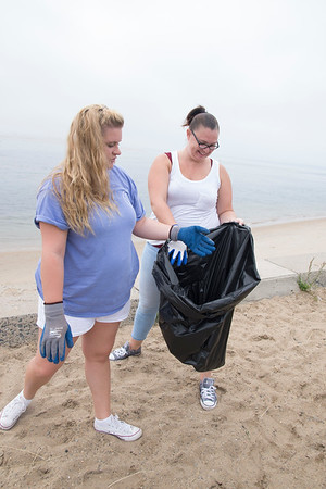 JIM VAIKNORAS/Staff photo Haylie Savoy and Tracy Leavitt, both of Salisbury, pick up long the seawall at Salisbury Beach Reservation Saturday. They were part of the COASTSWEEP, a state wide coastal cleanup sponsored by the Massachusetts Office of Coastal Zone Management.