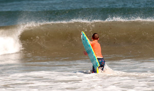 JIM VAIKNORAS/Staff photo A boy brave the cool weather to get a bit more summer in on Friday as he Boogie Boards on Salisbury Beach.