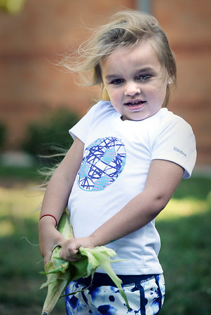 BRYAN EATON/Staff photo. Avery Rack, 5, then moved the corn down to use some leverage to try to shuck the ear of corn.