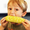 BRYAN EATON/Staff photo. Bennett Waddell, 5, bites in to enjoy the fruits, or grain, of he and his classmates' labor.