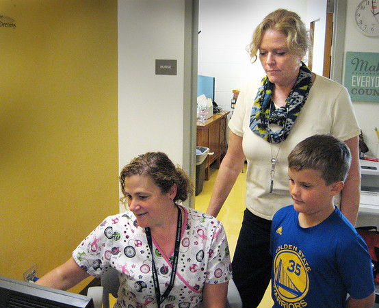 DYKE HENDRICKSON/Staff photo. Matthew Page, a fourth-grader at the Edward G. Molin Elementary School, stands with nursing supervisor Cathy Riccio, and nurse Michelle Rybicki, seated, as they view a new medical-software application that will be used in local schools.