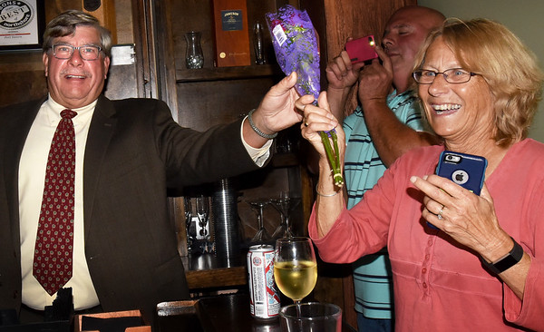 BRYAN EATON/Staff photo. Newburyport mayoral candidate Robert Cronin hands flowers to his wife, Sue, celebrating winning one of two spots in the final election in November along with encumbent Mayor Donna Holaday.