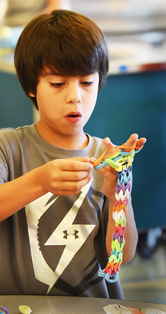 "BRYAN EATON/Staff photo. Daniel Lopez, 8, works on a ""looper"" in the YWCA's Afterschool Program at the Bresnahan School in Newburyport. Made out of elastic fabric, they weave the pieces into a rope to make necklaces or bracelets."