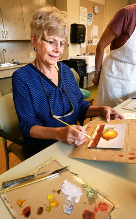 BRYAN EATON/Staff photo. The weekly oil painting class at the Newburyport Senior Center resumed Tuesday after a summer break with the class doing a still life of a lemon. Camille Papp of Newburyport, who is new at painting, puts the final touches on her canvas.
