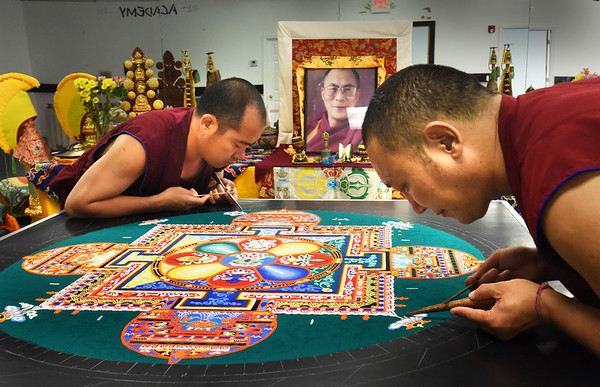 BRYAN EATON/Staff photo. Ven. Tashi Phuntsok, right, and Jampa Norbu create a sand mandala with two other monks from the Drepung Loseling Monastery at Unity on the RIver in Amesbury which is hosting the Mystical Arts of Tibet throughout the week. They and two others will be working on the painting today and Friday from 11:00 a.m. to 7:00 p.m. which is open to public viewing. The closing ceremony will be in the dedication garden behind the church Saturday at 4:00 p.m. and is open to the public where the painting will be dismantled and toss in the Powow River.