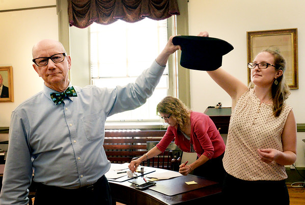 BRYAN EATON/Staff photo. Newburyport city clerk Richard Jones holds a hat as staffer Cassandra Green pulls names of candidates running for the councilor-at-large race Friday morning to determine in which order the names will appear.