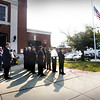 BRYAN EATON/Staff photo. The American flag was at half mast during a 9/11 memorial service held at the Amesbury Fire Station on Monday morning. Mayor Ken Gray, Police Chief William Scholtz and acting Fire Chief Jim Nolan lit candles of remembrance for the first responders and civilian casualties of 9/11.