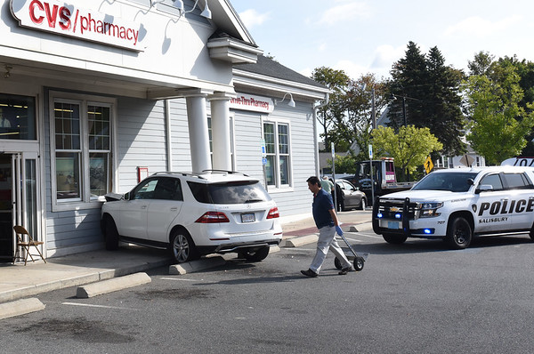 BRYAN EATON/Staff photo. An SUV jumped the curbing at CVS in Salisbury Square on Friday morning damaging a pillar. One person was transported to the Anna Jaques Hospital.