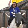 JIM VAIKNORAS/Staff photo Newbury Elementary School PTA president Liz Sforza rides a mechanical bull in the school gym Wednesday.