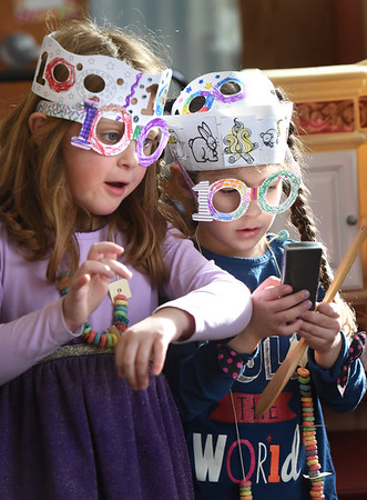 "BRYAN EATON/Staff photo. Maeve Goldson, 6, left, and Leila Allard, 5, make believe they have fancy watches while wearing their 100th Day of School costumes at Newbury Elementary School. The ""100th Day Lady"" came to the kindergarten classes where the kids made necklaces with 100 Fruit Loops, did counting excercises that added up to 100 then had a small party to celebrate."