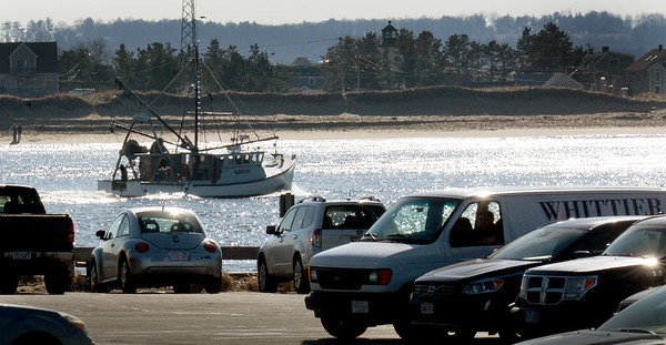 BRYAN EATON/Staff photo. A fishing boat motors up the Merrimack River adjacent to Salisbury Beach State Reservation on Tuesday past a couple dozen cars as people enjoyed another day of nice weather. Winter returns for the weekend after going to just above 50 degrees on Friday.