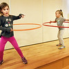 BRYAN EATON/Staff photo. Lexi Ranney, left, and Abby Bates, both 6, Hula Hoop to music in the Newburyport YWCA Afterschool Program at the Bresnahan School. Next week during school vacation the youngsters will be on several field trips througout the area.