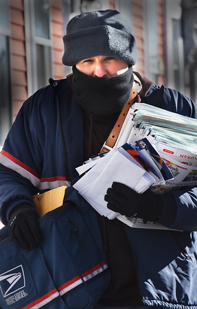 BRYAN EATON/Staff photo. The letter carrier makes his appointed rounds no matter what, which U.S. Post Officer letter carrier Chafik Haddadi proves as he delivers his mail in 10 degree weather on Water Street in Newburyport on Thursday morning. Weather for the weekend warms into the 30's and up to 50 in the early part of next week.