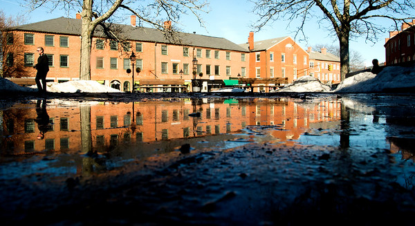 JIM VAIKNORAS/Staff photo Downtown Newburyport's North Row is reflected in a large puddle in Market Square Monday caused by ice and snow melted by warm weather.
