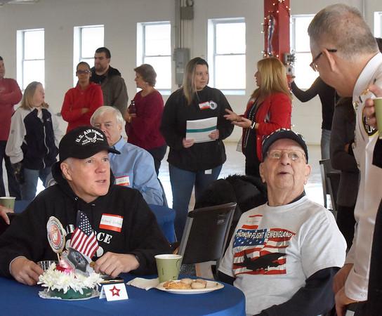 BRYAN EATON/Staff photo. World War II U.S. Navy veteran Herbert Erikson, sitting, right, and his son, U.S. Air Force Brigadier General, and chaplain, Richard Erikson, Ret., left, chat with Amesbury Police Chief William Scholtz.