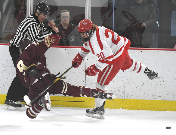 JIM VAIKNORAS/Staff photo Newburyport's Cade Beauparlant is checked by St John's Sean Clark during their game at the Graf Rink in Newburyport Friday.